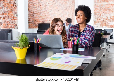 People laughing sitting office desk laptop colleagues fun joke business woman casual wear together