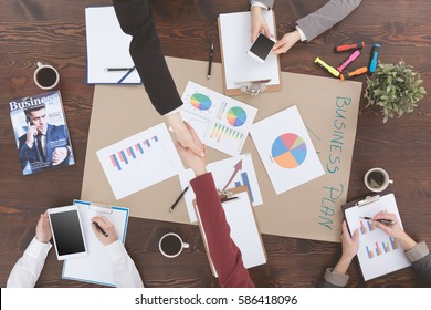 People leading successful business negotiations beside table, top view
