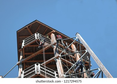 People learining safely the technic of climbing on a wooden building. saftey, worker, danger, climbing, fun, tourist, equipment;