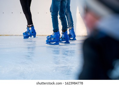 People, legs in blue skates on the ice rink in the open air spend time, play in the winter