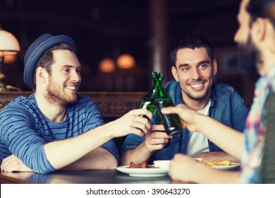 people, leisure, celebration, friendship and bachelor party concept - happy male friends drinking beer and clinking bottles at bar or pub