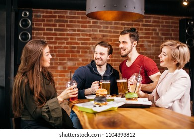 People, leisure, celebration and party concept - group of happy smiling friends clinking glasses with beer at bar or pub enjoying night out at Burger Bar