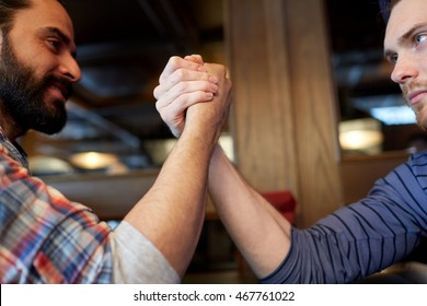people, leisure, challenge, competition and rivalry concept - close up of male friends arm wrestling at bar or pub