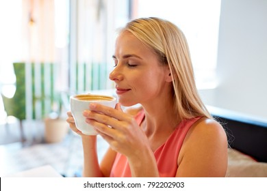 people and leisure concept - close up of happy woman drinking coffee at restaurant