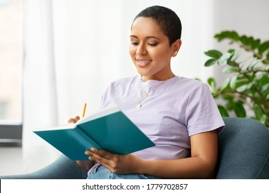 people and leisure concept - happy smiling african american woman with diary sitting in chair at home