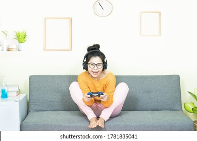 people and leisure concept - happy smiling asian young woman with gamepad playing video games on console having fun, resting on weekends at home under quarantine