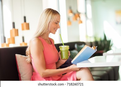 people and leisure concept - happy woman drinking green smoothie or vegetarian shake and reading book at restaurant or cafe