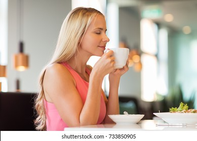 people and leisure concept - happy woman drinking coffee and eating at restaurant