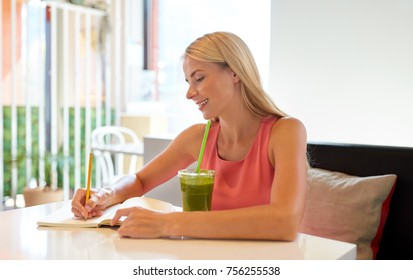 people and leisure concept - happy woman with green smoothie drink or vegetarian shake writing to notebook at restaurant or cafe