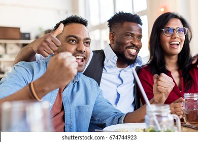 people, leisure and entertainment concept - happy fans or friends celebrating victory at bar or restaurant