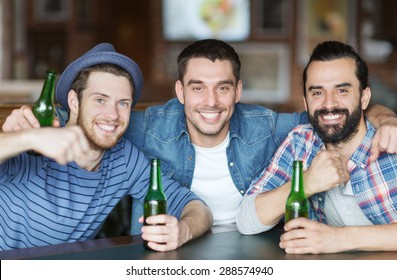 people, leisure, friendship and bachelor party concept - happy male friends drinking bottled beer and hugging at bar or pub