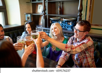 people, leisure, friendship and celebration concept - happy friends drinking draft beer and clinking glasses at bar or pub