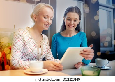 people, leisure, friendship and communication concept - happy young women meeting and drinking tea or coffee at cafe