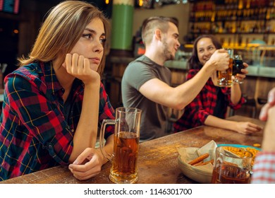 The people, leisure, friendship and communication concept - happy friends drinking beer, talking and clinking glasses at bar or pub and sad girl with negative emotions