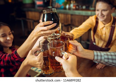 The people, leisure, friendship and communication concept - happy friends drinking beer, talking and clinking glasses at bar or pub
