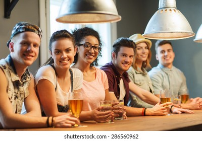 people, leisure, friendship and communication concept - group of happy smiling friends drinking beer, water or cocktails at bar or pub