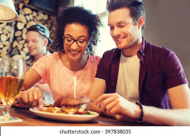 people, leisure, friendship, party and communication concept - group of happy smiling friends eating burger together at bar or pub