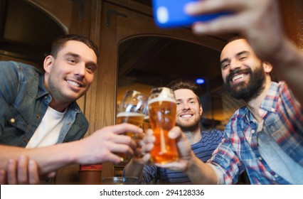 people, leisure, friendship, technology and bachelor party concept - happy male friends with smartphone taking selfie and drinking beer at bar or pub