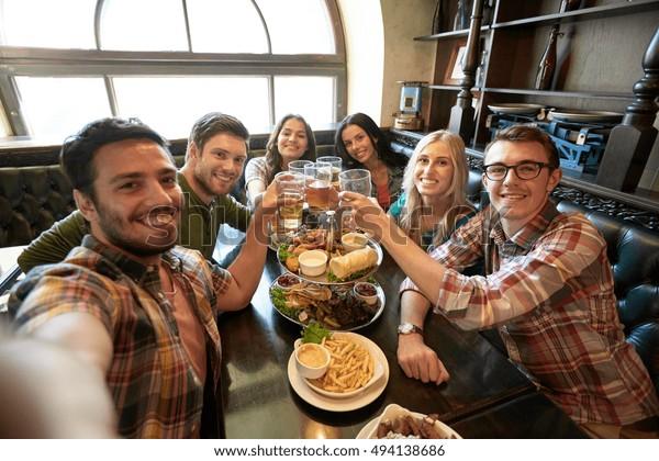 人々、レジャー、友情、テクノロジーのコンセプト – 幸せな友人が自分で飲み、ビールを飲み、バーやパブでスナックを食べる