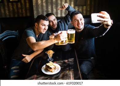 people, leisure, friendship, technology and party concept - happy male friends taking selfie and drinking beer at bar or pub
