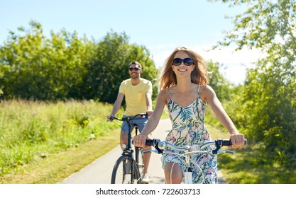 people, leisure and lifestyle concept - happy young couple riding bicycles along road in summer