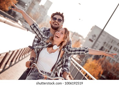 People, leisure and lifestyle concept-happy young couple riding bicycle in the city.