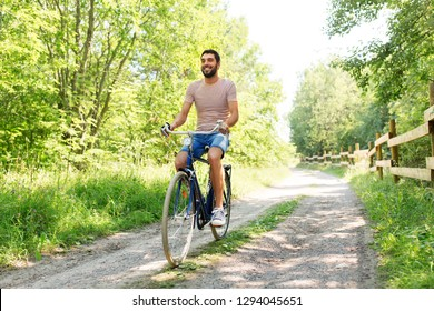 people, leisure and lifestyle - happy man riding fixie bicycle at summer park