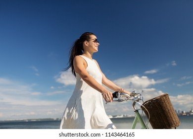 people, leisure and lifestyle - happy young hipster woman in summer dress with fixie bicycle at seaside