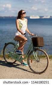 people, leisure and lifestyle - happy young hipster woman riding fixie bicycle at seaside in summer
