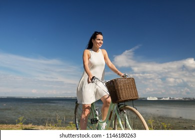 people, leisure and lifestyle - happy young hipster woman in summer dress riding fixie bicycle at seaside