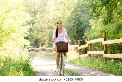 people, leisure and lifestyle - happy young woman riding fixie bicycle with basket at summer park