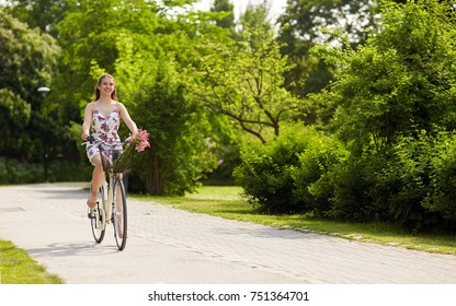 people, leisure and lifestyle - happy young hipster woman wearing summer dress riding fixie bicycle with wild flowers in basket at park
