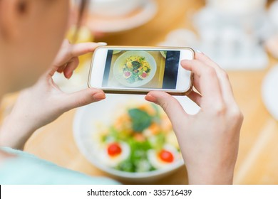 people, leisure and technology concept - close up of woman hands with smartphone taking picture of food at restaurant