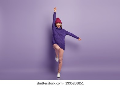People, life, energy concept. Elated young woman raises hands while jumps up in air, rejoices hearing good news, being in high spirit, wears warm headgear, knitted jumper and white sneakers.