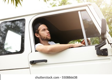 People, lifestyle, adventure and extreme concept. Young bearded traveler or adventurer sitting inside his white vehicle, driving alone towards national park, planning to spend vacations on safari trip