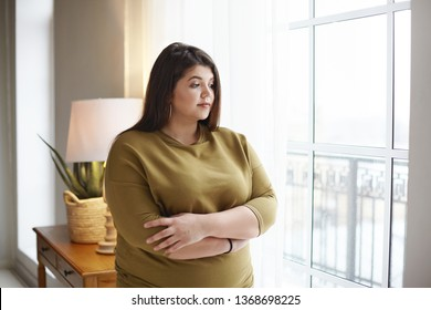 People, lifestyle and body positivity concept. Beautiful young brunette female with extra pounds standing by window at home, crossing arms on her chest, having thoughtful pensive look, pondering