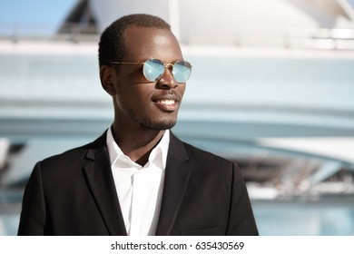 People, lifestyle, business, career and success. Portrait of handsome successful young Afro American entrepreneur wearing black suit and stylish sunglasses posing outdoors in urban surroundings