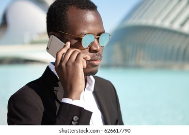 People, lifestyle, business and modern technology. Confident Afro American businessman wearing black formal suit and round mirrored lens shades checking voicemail on his way back to office after lunch