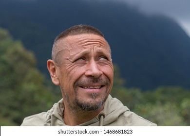 People and lifestyle concept. Happy middle-aged unshaven man outdoor against green nature background. Adult man portrait close up