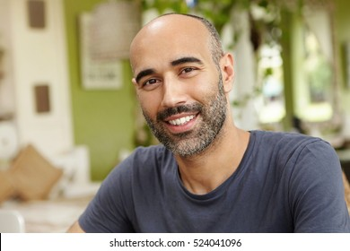 People and lifestyle concept. Happy middle-aged unshaven man wearing casual t-shirt looking at camera with cheerful smile while having lunch at outdoor cafe sitting against green interior background