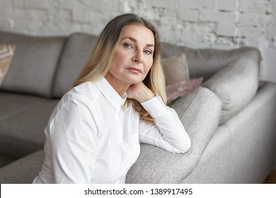People and lifestyle concept. Indoor shot of elegant beautiful sixty year old senior female wearing white shirt relaxing in living room sitting on comfortable sofa and adjusting her loose dyed hair