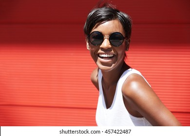 People and lifestyle concept. Portrait of fashionable African woman wearing round hipster sunglasses and short pixie haircut looking at the camera, smiling, laughing, showing her white teeth