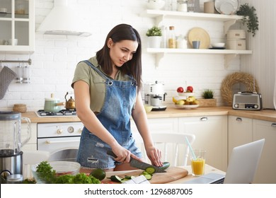 People, lifestyle, healthy eating, cooking and dieting concept. Positive young brunette woman standing at kitchen table, chopping green cucumber for dinner, watching culinary TV show online on laptop