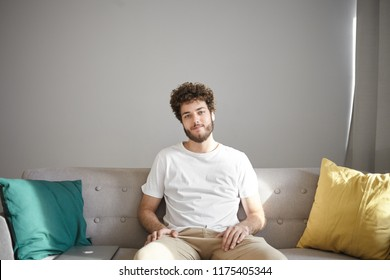People, lifestyle, interior and design concept. Cheerful attractive young Caucasian man with stubble and stylish wavy hairdo sitting on comfortable couch with decorative pillows and smiling