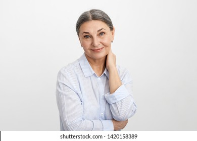 People, lifestyle, mature age and retirement concept. Attractive stylish European female pensioner with gathered gray hair holding hand on back of her neck and looking at camera with joyful smile