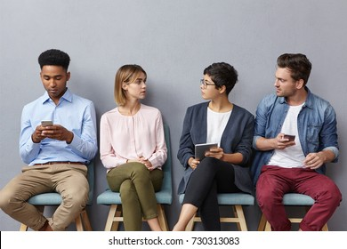 People, lifestyle and modern technologies concept. Young talented enterpreneurs have discussion, sit on chairs in queue, being addicted from electronic devices. Four managers chatt together indoor