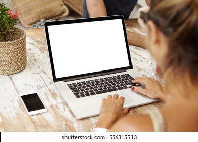 People, lifestyle, modern technology and communication concept. Young Caucasian female writer keyboarding on laptop while working on her new article for online women's magazine. View form back