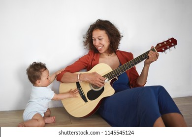 People, lifestyle, motherhood and childcare concept. Indoor shot of cheerful young Hispanic mother holding guitar, playing songs to her sweet bay boy, sitting on floor against white wall background