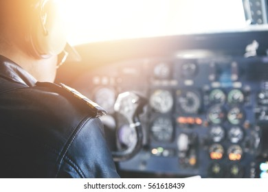 People, lifestyle and occupation concept. Rear view of commercial pilot wearing headset and uniform sitting inside aircraft cockpit in front of dashboard with numerous buttons. Film effect, flare sun