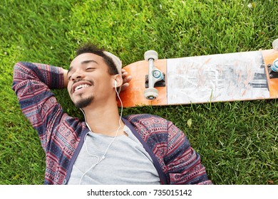 People, lifestyle, sport, enjoyment, leisure and hobby concept. Horizontal shot of stylish black man with beard, lies on green lawn, has happy expression as listens to music, rests after skateboarding
